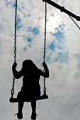 foto of young girls  - A silhouette of a sad young girl swinging alone - JPG