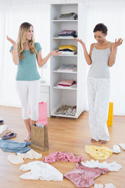 pic of scat  - Two happy young women looking down at shopping bag and scatted clothes on floor at home - JPG