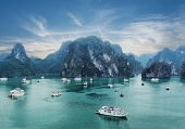 pic of barge  - Tourist junks floating among limestone rocks at early morning in Ha Long Bay South China Sea Vietnam Southeast Asia - JPG