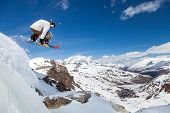 stock photo of snowboarding  - Jumping snowboarder keeps one hand on the snowboard on blue sky background - JPG