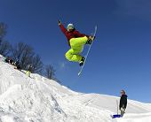image of snowboarding  - Jumping snowboarder keeps one hand on the snowboard on blue sky background - JPG