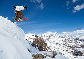 picture of snowboarding  - Jumping snowboarder keeps one hand on the snowboard on blue sky background - JPG