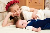 picture of emo-boy  - Older sister hugging baby lying on the bed - JPG