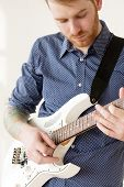 stock photo of ginger man  - Handsome man playing on guitar - JPG