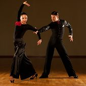 stock photo of waltzing  - Professional ballroom dance couple preform an romantic exhibition dance - JPG