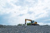 foto of power-shovel  - Image of a wheeled excavator on a quarry tip with extra shovel and airplane starting in the background - JPG