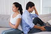 stock photo of not talking  - Couple not talking after a dispute on the sofa at home in the living room - JPG
