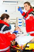 stock photo of accident victim  - Emergency doctor and nurse or ambulance team medicate accident victim - JPG