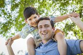foto of piggyback ride  - Mixed Race Father and Son Playing Piggyback Together in the Park - JPG