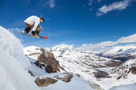 pic of snowboarding  - Jumping snowboarder keeps one hand on the snowboard on blue sky background - JPG