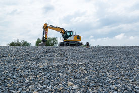 stock photo of power-shovel  - Image of a wheeled excavator on a quarry tip with extra shovel - JPG