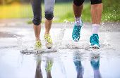 foto of rainy weather  - Young couple running on asphalt sports field in rainy weather - JPG