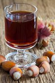 picture of hazelnut  - Homemade Hazelnut liqueur in a glass and hazelnuts of an old rustic wooden table - JPG