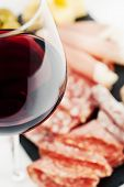 stock photo of charcuterie  - Glass of red wine with charcuterie assortment on the background - JPG