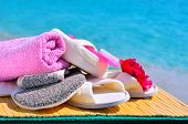 picture of pumice stone  - Natural bath sponges bath slippers pumice and towel against blue ocean - JPG