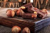 stock photo of wood pieces  - Pile of delicious chocolate bars with whole nuts on wood Warm composition of chocolate pieces with hazelnuts - JPG