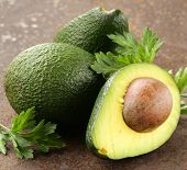 foto of avocado  - fresh organic ripe avocado with leaves of parsley - JPG