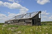 pic of dairy barn  - An old barn has deteriorated so only the framework remains along with a few areas of siding