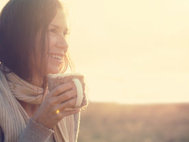 picture of cold drink  - Woman wearing warm knit clothes drinking cup of hot tea or coffee outdoors in sunlight - JPG