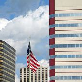 stock photo of reach the stars  - Buildings of varying designs and a flag of the United States of America flying in the breeze reach into a blue sky filled with puffy clouds - JPG