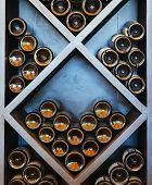 stock photo of racks  - wine rack bottles stacked on wooden racks - JPG