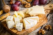 picture of brie cheese  - Mix Cheese: Emmental Camembert Parmesan blue cheese with walnuts and grape on wooden table