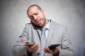 picture of stress  - Stressed businessman talking on many phones at once - JPG