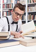 image of nerd  - Concentrated young nerd man in shirt and bow tie reading book and pointing it - JPG