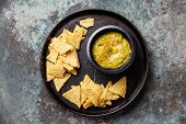 stock photo of nachos  - Fresh guacamole dip with nachos chips on metal background - JPG