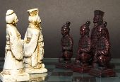 stock photo of humility  - White King and Queen standing in front of a black king and his warriors - JPG
