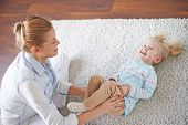 stock photo of babysitter  - Young female or babysitter playing with little girl on the floor - JPG