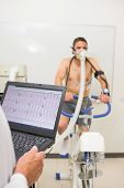 stock photo of exercise bike  - Man doing fitness test on exercise bike at the medical centre - JPG