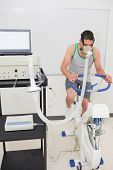 image of breathing exercise  - Man doing fitness test on exercise bike at the medical centre - JPG