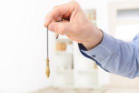 stock photo of pendulum  - Hand with pendulum - JPG