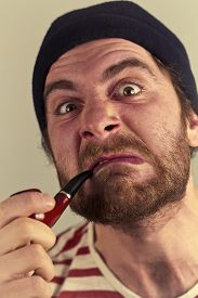 stock photo of wacky  - Mean bearded sailor grimacing while smoking a pipe - JPG