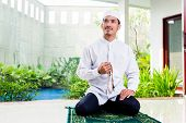 picture of prayer beads  - Asian Muslim man praying at home sitting on prayer carpet in his house in front of the tropical garden - JPG