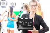 stock photo of tv sets  - Woman with take clap or board on Film Set of video production for TV - JPG