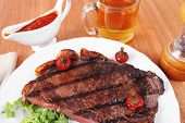 foto of chili peppers  - rural design new york meat style beef steak fillet on white plate with hot chili pepper served with tea cup ketchup in Gravy boat pepper mill and cutlery on napkin on wooden table - JPG