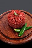 pic of hamburger-steak  - very big raw hamburger cutlet with sprouts and chilli pepper on wooden plate over black background - JPG