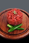 picture of hamburger-steak  - very big raw hamburger cutlet with sprouts and chilli pepper on wooden plate over black background - JPG