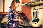 image of stir fry  - Woman in kitchen cooking stir fry frozen vegetables - JPG