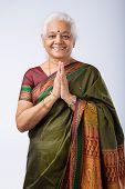 picture of namaste  - Senior Indian woman in namaste pose smiling - JPG