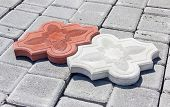 picture of interlocking  - One red and one white concrete curly interlocking pavers with ornament on the surface of another gray paver on depot - JPG