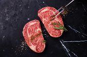stock photo of ribeye steak  - Two Raw fresh marbled meat Black Angus Steak Ribeye seasonings and meat fork on dark marble background - JPG