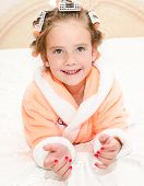 pic of hair curlers  - Happy funny little girl with manicure and hair curlers in bathrobe lying on bed - JPG