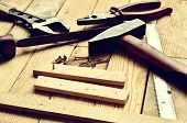image of pliers  - Hammer flat file pliers monkey wrench screws boards and blade on natural wooden background - JPG