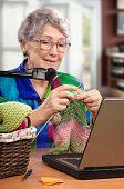 pic of knitting  - Vertical portrait of aged woman learning the basics of knitting via internet - JPG