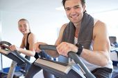 pic of elliptical  - Handsome Muscular Young Guy Smiling at the Camera While Exercising on Elliptical Bike with his Partner Next to him Inside the Fitness Gym - JPG