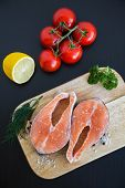 stock photo of salmon steak  - upper view of two salmon steaks on a wooden board with a balck background - JPG