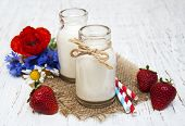 picture of wildflowers  - Bottles of milk with strawberry and wildflowers on a old wooden background - JPG